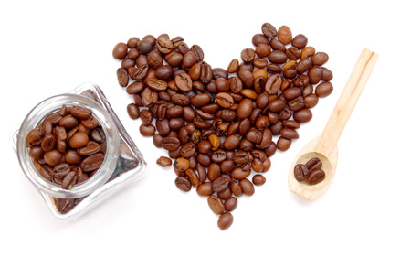 Heart from coffee beans, glass and spoon on a white background