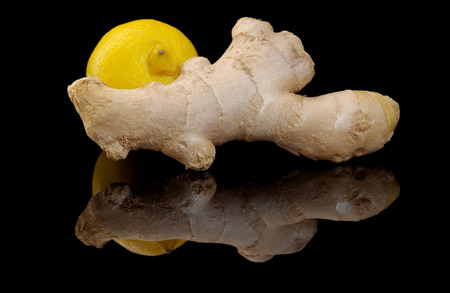Ginger and lemon on a black background with reflection Stockfoto