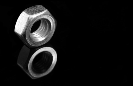 Metal nuts on black background with reflection Stock Photo