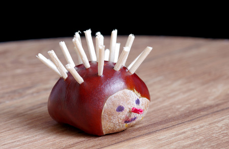 Hedgehog made from chestnut on wooden table Stock Photo