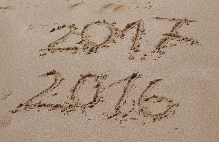 End of 2016, beginning of 2017 written in the sand on the beach