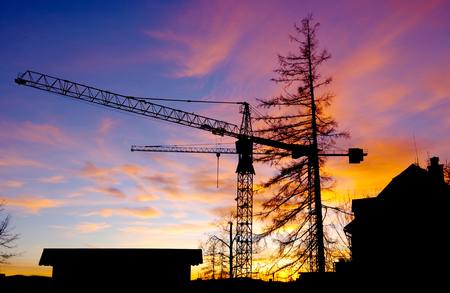 Sunset and beautiful sky with trees, building and construction crane