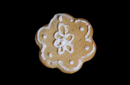 Gingerbread in the shape of a flower on black background