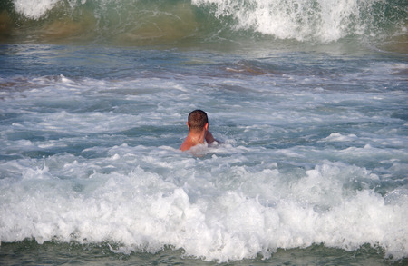 big waves: A man swims in the sea in big waves