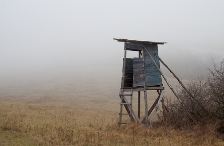 Hunting high watchtower on autumn in fog