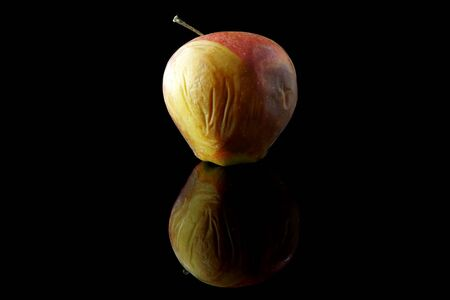 Rotting apple on black background with reflection