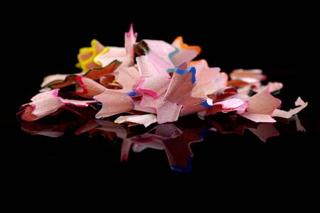 Pencil Shavings on a black background with reflection