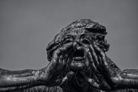 Statue with a gesture of call. Head of sculpture with open mouth and hands. Background of pure sky. Black and white photo.