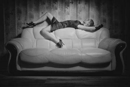 girl posing on a white sofa in a black dress photo