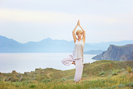 meditating woman: Senior woman doing yoga exercises with mountain on the background