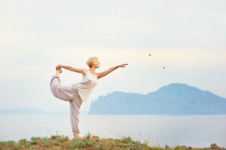 背景に山とヨガの練習をしている年配の女性 写真素材