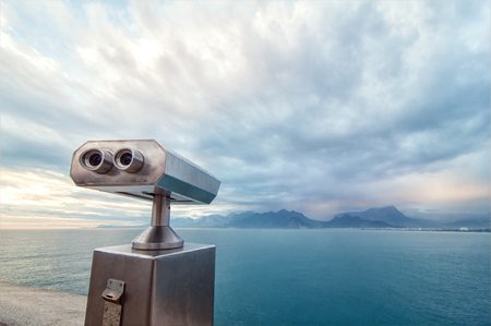 Coin Operated Binocular viewer next to the waterside promenade in Antalya looking out to the Bay and city. Landscape with beautiful cloudy sky, sea and mountains.. Stock Photo