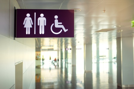 public toilet: Toilets icon. Public restroom signs with a disabled access symbol. Interior of airport terminal.