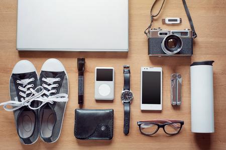 Outfit współczesnego podróżnika, student, kobieta czy facet. Narzut zasadniczych na tle drewniane: aparat, inteligentnego telefonu, szklanki, latarki, laptop, portfel, zegarek Półbuty gumowe, termos,, multitool, odtwarzacz MP3