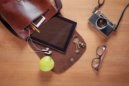 Outfit of traveler, student, teenager, young man. Overhead of essentials for modern young person. Different objects on wooden background: leather bag, camera, smartphone, glasses, keys, digital tablet