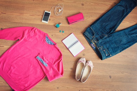 girl in jeans: Outfit of young woman. Essentials for modern young lady. Different female accessories on wooden floor ballet flats, jeans, smart phone, note book, sweatshirt, nail polish, clutch, earrings Stock Photo