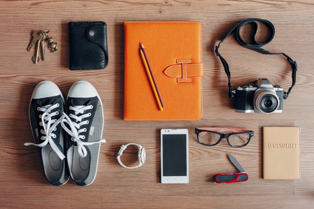 Outfit of traveler, student, teenager, young woman or guy. Overhead of essentials for modern young person. Different photography objects on wooden background. Items include keys, camera, smart phone, glasses, passport, digital tablet, wallet, folder, watc