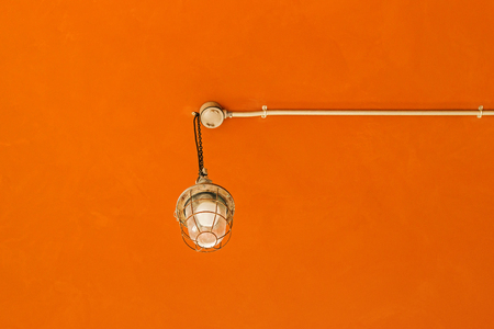 Vintage lamp on the ceiling with orange cement background.