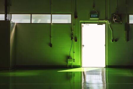 Exit door and green floor area with light from the sun.