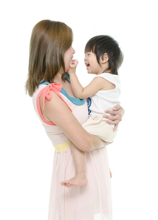 Asian mother and baby kissing, laughing and hugging photo