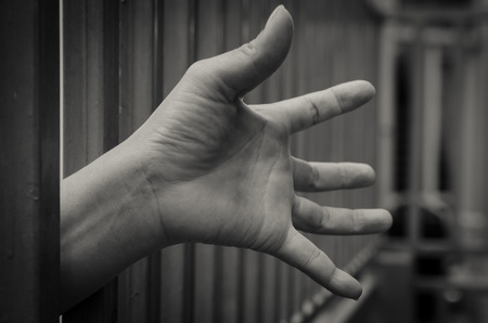 confined: Hand in jail Stock Photo