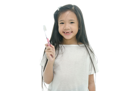 Little beautiful asian girl brushing teeth,missing teeth