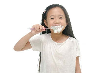 Little beautiful asian girl brushing teeth photo