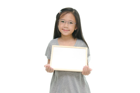 Little Asian girl holding empty whiteboard on white background photo