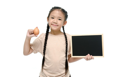 Little asian girl holding egg and black board photo