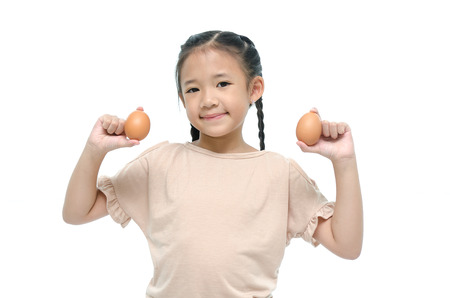Little asian girl smiiing and holding egg photo