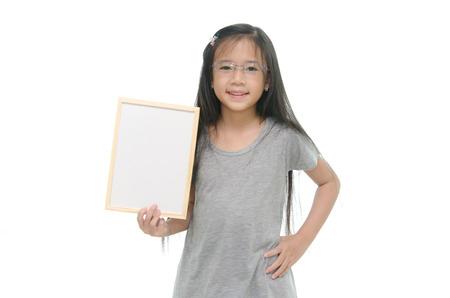 Little Asian girl holding empty whiteboard on white background photo