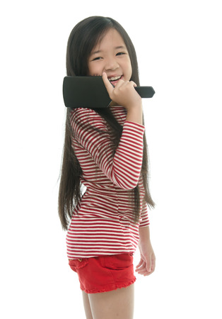Little asian girl smiling and brushing hair on white background isolated photo