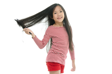 Little asian girl smiling and brushing hair on white background isolated