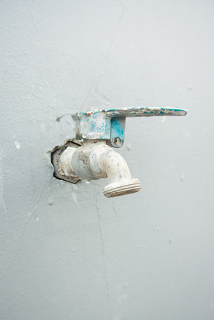 Old water tap on concrete wall photo