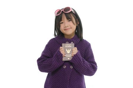 Little asian girl holding passport on white background isolated photo