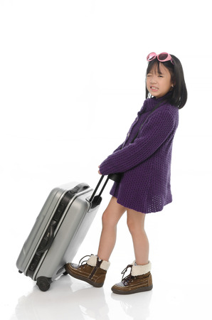 Little asian girl pulling heavy baggage on white background isolated photo
