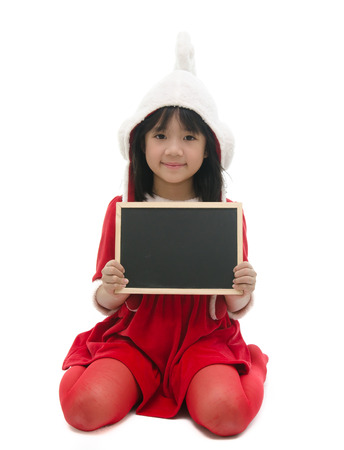 Asian girl in santa costume sitting and holding chalkboard on white background photo