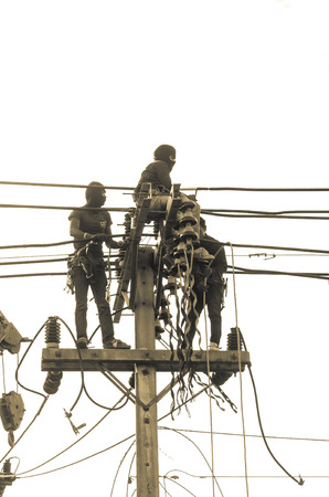 climbing cable: Three Asian electrician climb high in pole to work without safeguard Stock Photo