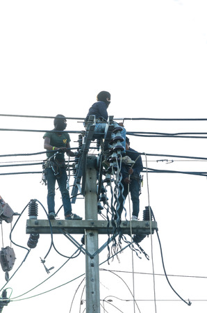 Three Asian electrician climb high in pole to work without safeguard photo