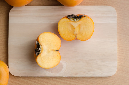 trencher: Close up of persimmon on wooden table with copy space Stock Photo