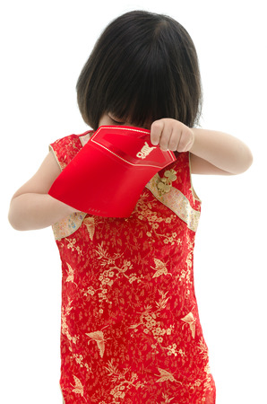 Asian baby holding ang pow or red packet monetary gift on white background isolated photo