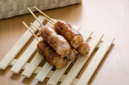 Thai style grilled pork and vermicelli or Wun Sen sausages on wooden table with copy space photo