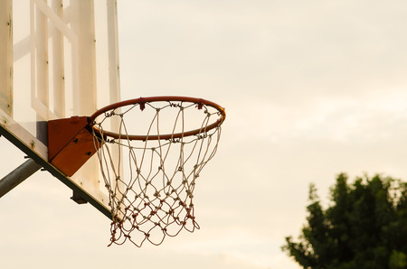 Close up of a basketball hoop, under the sunset. photo