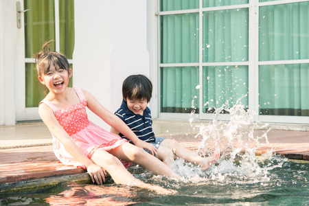 swimming pool home: Asian children splashing around in the pool on a hot sunny summer day Stock Photo