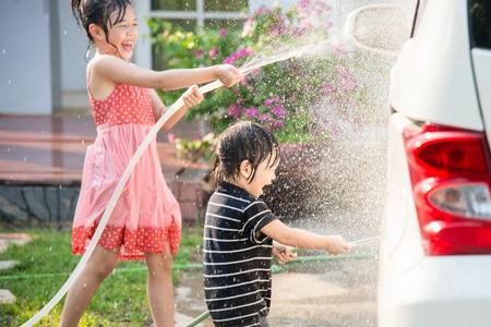 carwash: Niños asiáticos lavan coche en el jardín Foto de archivo