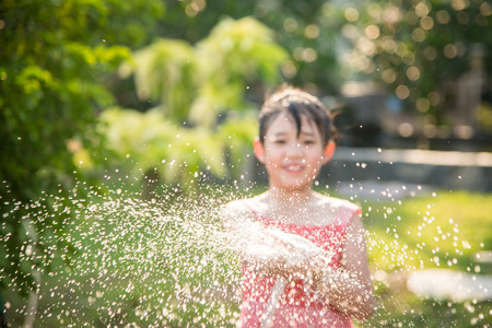 Blur background of Asian girl playing with water hose outdoors in the garden at the backyard of the house on a hot sunny summer day