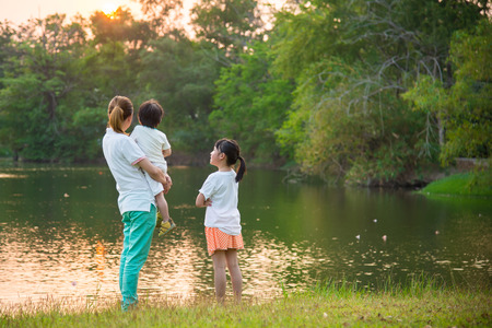 Asian mother holding son and talking with daughter at the beautiful lake on sunset