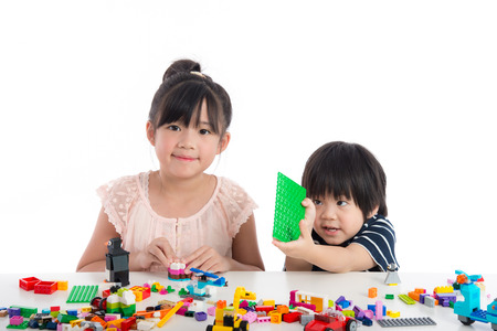Little asian children  playing with colorful construction blocks on white background isolated