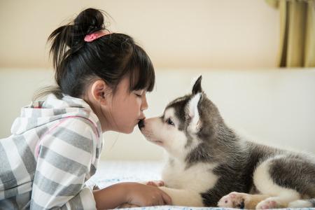 Weinig Aziatisch meisje kussen van een Siberische husky puppy op bed