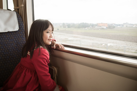Little asian girl looking through window. She travels on a train,vintage filter photo